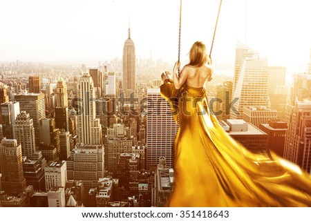 Woman on a swing above New York City - stock photo
