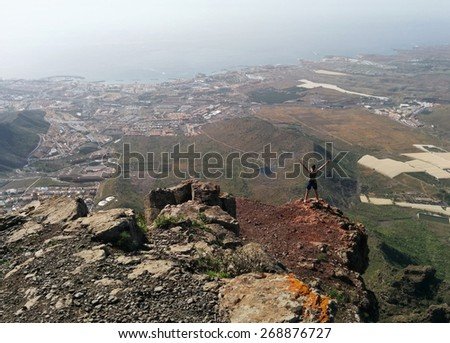 Woman on a top of a mountain enjoying valley view. Tenerife, Canary Islands, Spain - stock photo
