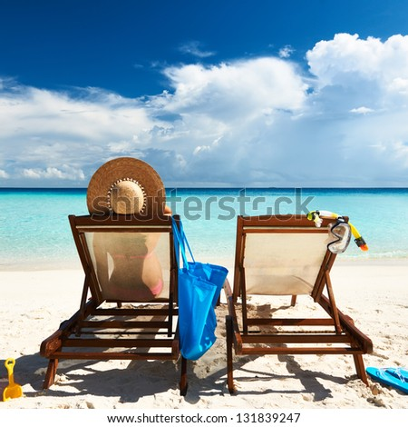Woman on a tropical beach in chaise lounge at Maldives - stock photo