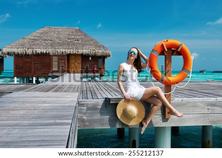 Woman on a tropical beach jetty at Maldives - stock photo