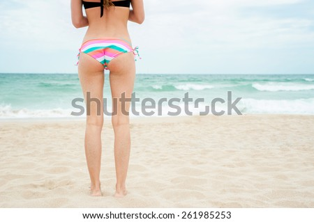 Woman on beach, Rear view of young beautiful girl wearing bikini, standing back looking to sea blue sky horizon, vacation concept of travel ocean. Close-up,no face. - stock photo