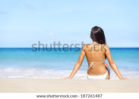 Woman on beach sitting in sand looking at ocean enjoying sun and summer travel holidays vacation getaway. Girl in bikini relaxing under blue sky. - stock photo