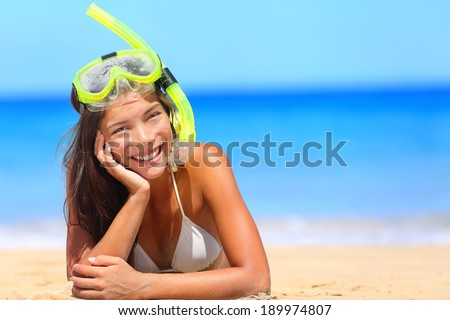 Woman on beach vacation holidays with snorkel lying in sand with snorkeling mask and fins smiling happy enjoying the sun on sunny summer day. Multi ethnic Asian Chinese / Caucasian woman model. - stock photo