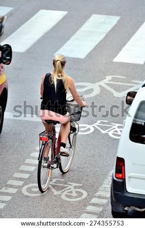 Woman on bike waiting for green light in bike lane - stock photo