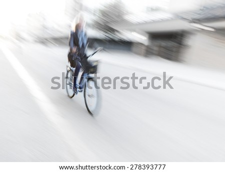 Woman on blue bike in blurred motion in city - stock photo