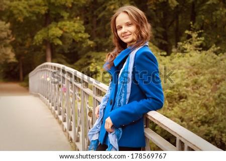 woman on bridge in autumn park - stock photo