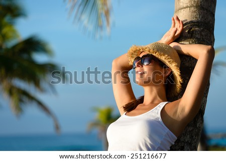 Woman on caribbean travel relaxing and resting under tropical palm trees. Happy brunette enjoying vacation and tranquility. - stock photo