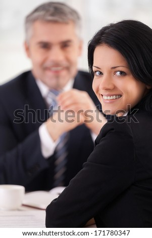 Woman on interview. Cheerful young woman in formalwear looking over shoulder and smiling while mature man in suit sitting on background - stock photo