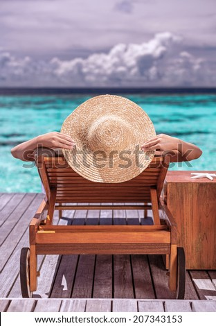 Woman on luxury beach resort, female tanning on sunbed, female wearing a big stylish hat, young girl enjoying beautiful seascape, relaxation on summer travel,  tourism concept - stock photo
