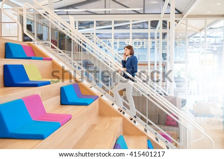 Woman on mobile phone walking up stairs in colourful office  - stock photo