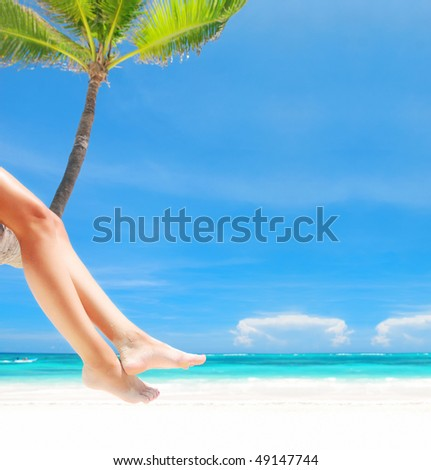 Woman on palm on caribbean beach - stock photo