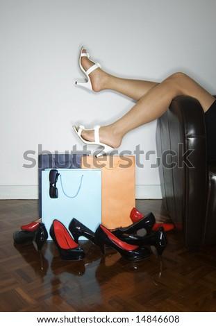 woman on sofa next to shopping bags - stock photo