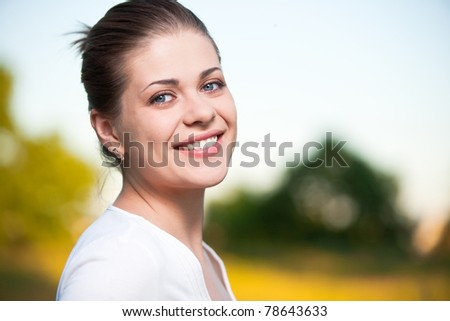Woman on summer sky and tree background. Outdoor portrait with big smile. - stock photo