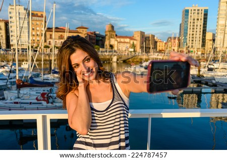 Woman on summer vacation travel taking selfie photo with smartphone camera at Gijon harbor, Asturias, Spain. Happy tourist having fun in european city. - stock photo