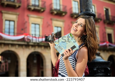 Woman on summer vacation travel through Spain, having fun while visiting typical spanish landmark.  Female tourist holding tourism guide map and camera. Plaza Mayor of Gijon, Asturias, Spain. - stock photo