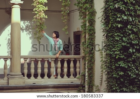 woman on the balcony with antique stone columns and a statue - stock photo
