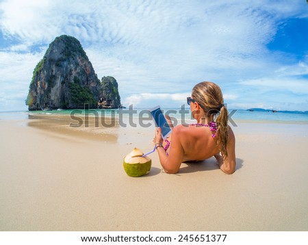 Woman on the beach in Thailand using her computer tablet - stock photo