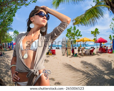 Woman on the beach of Kuta in Bali Indonesia with surf boards on background - stock photo