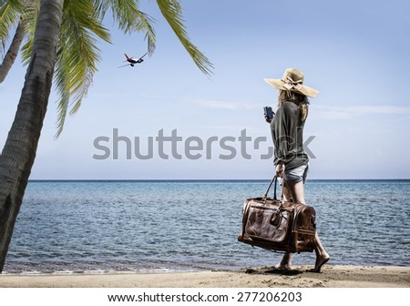 Woman on the beach with vintage leather bag - Travel concept - stock photo