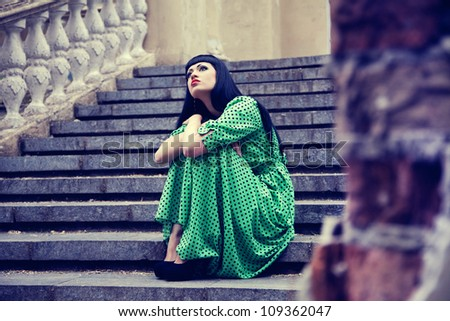Woman on the old stairs in green dress - stock photo