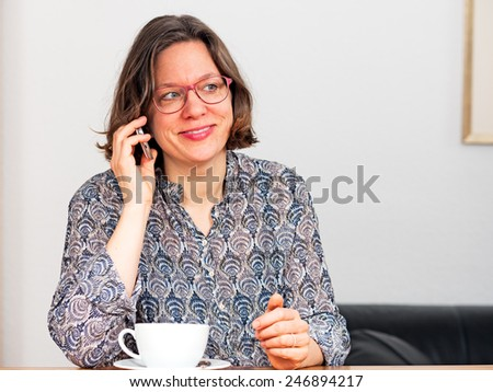 Woman on the phone with cappuccino cup - stock photo