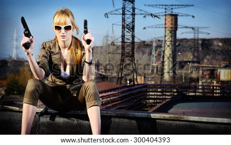 Woman on the roof with guns - stock photo