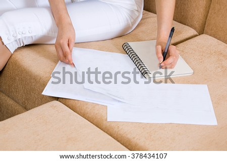 woman on the sofa hold papers - stock photo