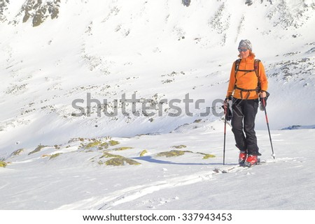 Woman on touring skis traversing along sunny plateau in winter - stock photo