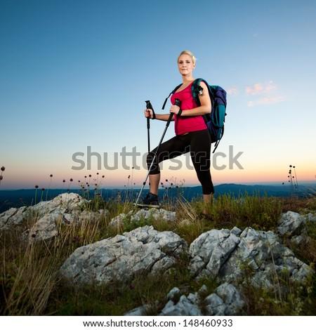 Woman on trekking - Beautiful blonde girl hiking on mountains - stock photo
