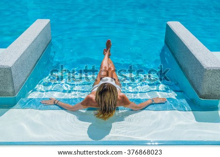 Woman on vacation relaxing by the swimming pool - stock photo