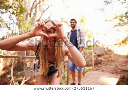 Woman On Walk With Man Making Heart Shape At Camera - stock photo