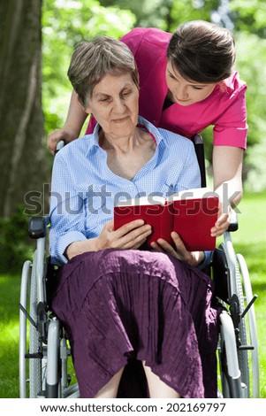 Woman on wheelchair reading book in a garden - stock photo