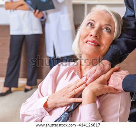 Woman on wheelchair smiling asking for help. Healthcare concept. - stock photo