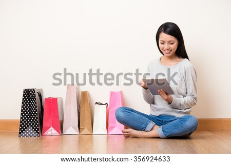 Woman online shopping though tablet pc - stock photo
