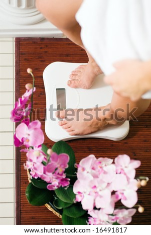 Woman (only feet to be seen) standing on a scale in a spa setting - stock photo