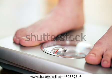 Woman (only feet to be seen) standing on bathroom scale measuring her weight controlling her dieting results - stock photo