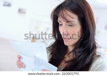 Woman opening a letter - stock photo