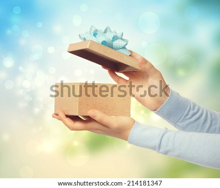 Woman opening and presenting gift box on bright background - stock photo