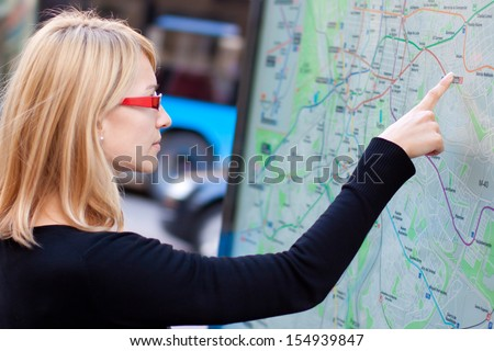 Woman orientating herself on the public transport map. - stock photo