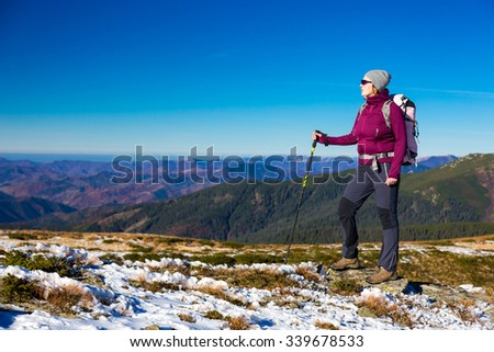 Woman Outdoor Hiker Sporty Clothing Staying with Backpack and Walking Poles on Mountain Snowy Trail Enjoying Stunning Landscape View - stock photo