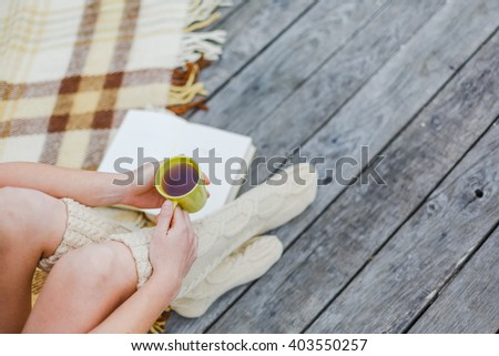 woman outdoor with book and cup of tea in hands, top view point. Cozy, comfy, soft - stock photo