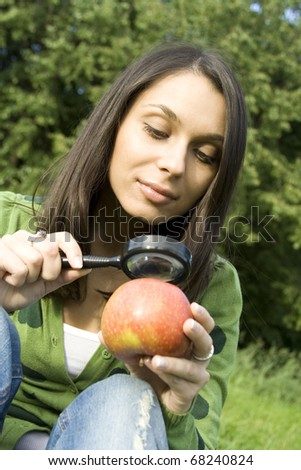 Woman outdoors sitting on the green grass checks apple is natural, looks at him through a magnifying glass - stock photo