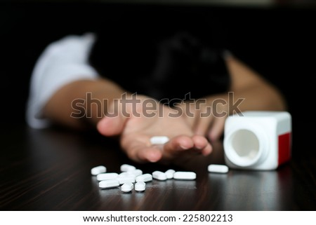 Woman overdose and had a pills in her hand - stock photo