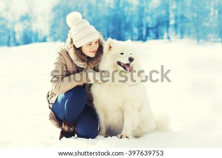 Woman owner hugging white Samoyed dog in winter park - stock photo