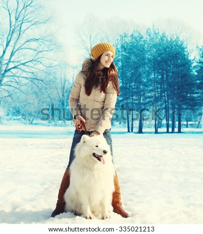 Woman owner walking with white Samoyed dog in winter park - stock photo