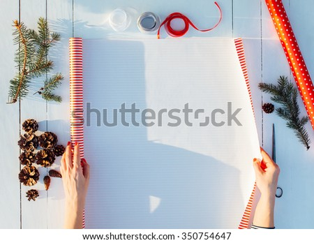 Woman packing gift in red paper with blank space on a wooden background for Christmas, New Year, Birthday, Mother's day or Valentine - stock photo