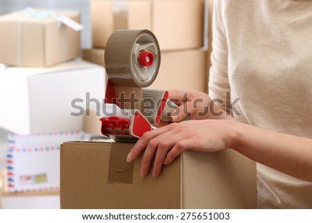 Woman packs parcel in post office - stock photo