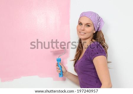 woman painting baby nursery pink - stock photo