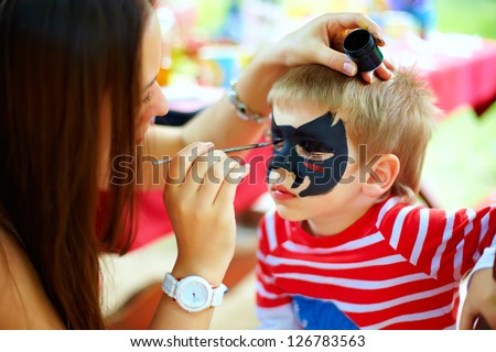 woman painting face of kid outdoors - stock photo