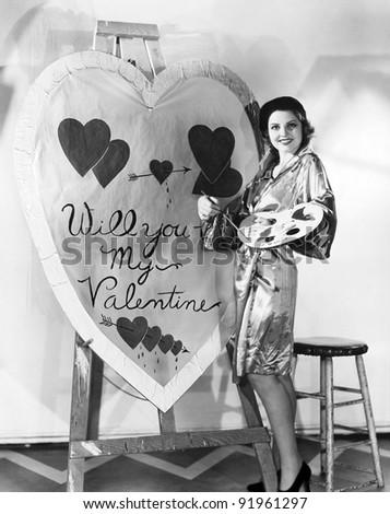 Woman painting huge valentine - stock photo